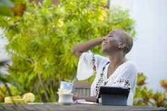Jeune femme afro-américaine noire heureuse et attirante travaillant avec le comprimé dehors au thé potable décontracté ou au café Photo stock