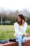 Jeune femme afro-américaine s'asseyant en beau parc regardant loin Photos stock