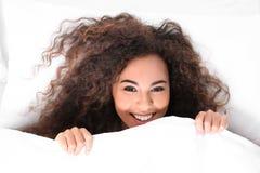 Jeune femme afro-américaine se trouvant sous la couverture bedtime photos libres de droits