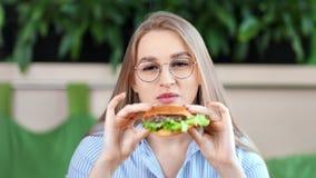 Jeune femme agréable heureuse de portrait en gros plan mangeant le gros hamburger savoureux regardant la caméra banque de vidéos