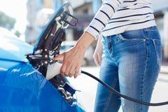 Jeune femme agréable tenant un chargeur de voiture Photographie stock libre de droits