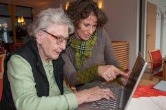 Jeune femme aidant le fonctionnement supérieur de femme avec l'ordinateur portable photo stock