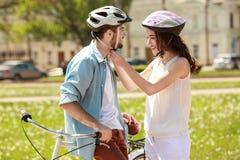 Jeune femme aidant son ami à mettre dessus le casque de bicyclette Images libres de droits