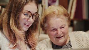 Jeune femme aidant une vieille femme supérieure avec l'ordinateur portable banque de vidéos