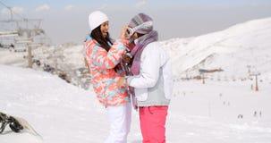 Jeune femme ajustant ses lunettes de ski d'amis Image stock