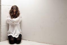 Jeune femme aliénée avec la camisole de force sur des genoux images stock