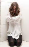 Jeune femme aliénée avec la camisole de force sur des genoux photo libre de droits