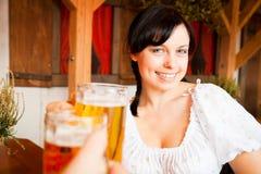 Jeune femme allemande appréciant une tasse de bière photographie stock libre de droits