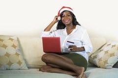 Jeune femme américaine d'africain noir heureux et attirant en Santa Claus à l'aide de la carte de crédit et de l'ordinateur porta photographie stock
