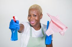 Jeune femme américaine de beau et heureux africain noir à l'aide de la bouteille détersive de jet comme nettoyage et lavage espiè photo libre de droits