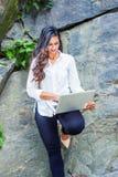 Jeune femme américaine indienne est avec de longs cheveux travaillant sur l'ordinateur portable extérieur à New York images libres de droits