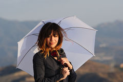Jeune femme amicale avec le parapluie au coucher du soleil Photo stock