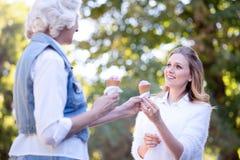 Jeune femme amusée appréciant la crème glacée avec la mère âgée dehors Photos libres de droits