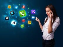 Jeune femme appelant par le téléphone avec de divers graphismes Photos libres de droits