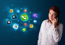 Jeune femme appelant par le téléphone avec de divers graphismes Image stock