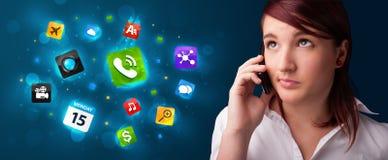 Jeune femme appelant par le téléphone avec de divers graphismes Photographie stock libre de droits