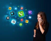Jeune femme appelant par le téléphone avec de divers graphismes Photos stock