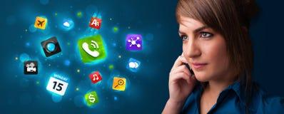 Jeune femme appelant par le téléphone avec de diverses icônes Image libre de droits