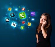 Jeune femme appelant par le téléphone avec de diverses icônes Photo stock