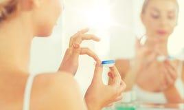 Jeune femme appliquant des verres de contact à la salle de bains images stock