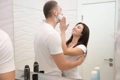 Jeune femme appliquant doucement la mousse pour un homme au rasage image stock