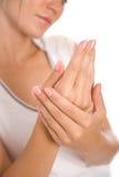 Jeune femme appliquant la crème aux mains Photo stock
