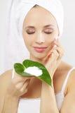 Jeune femme appliquant la crème cosmétique Image libre de droits