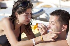 Jeune femme appliquant la crème de soleil-protection sur son ami Photographie stock libre de droits