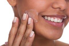 Jeune femme appliquant la crème sur son visage photographie stock