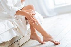 Jeune femme appliquant la lotion de corps sur des jambes Photographie stock