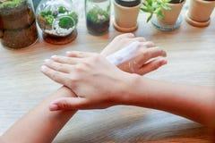 Jeune femme appliquant la lotion de crème hydratante de mains sur la table en bois Image libre de droits