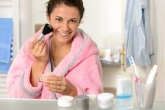 Jeune femme appliquant la poudre de visage avec la brosse Photo stock