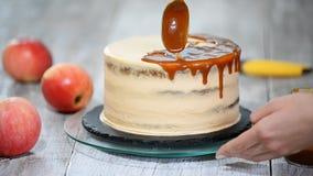 Jeune femme appliquant la sauce à caramel sur le gâteau fait maison délicieux à la table Gâteau délicieux avec la pomme et la crè clips vidéos