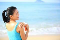 Jeune femme appliquant le corps de crème de bloc du soleil photos stock
