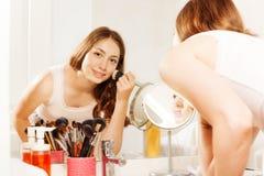 Jeune femme appliquant le maquillage avec la brosse de poudre de visage photos stock