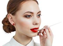 Jeune femme appliquant le rouge à lèvres avec un applicateur image libre de droits