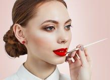 Jeune femme appliquant le rouge à lèvres avec un applicateur photographie stock