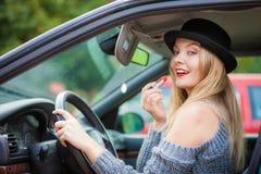 Jeune femme appliquant le rouge à lèvres dans la voiture images stock
