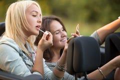 Jeune femme appliquant le rouge à lèvres dans la voiture Photo libre de droits