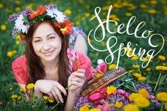 Jeune femme appréciant l'odeur dans un jardin fleurissant de ressort avec le sprint de lettres bonjour Image stock