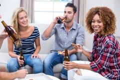 Jeune femme appréciant la bière et la pizza avec des amis Images stock