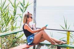 Jeune femme appréciant la boisson froide dans une barre de plage photos libres de droits
