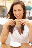 Jeune femme appréciant la cuvette de café Photo stock
