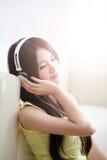 Jeune femme appréciant la musique à la maison Image libre de droits