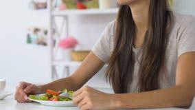 Jeune femme appréciant la salade de légume frais se reposant sur la cuisine confortable banque de vidéos