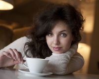 Jeune femme appréciant le café de latte en café Photos libres de droits