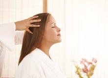 Jeune femme appréciant le massage principal Photographie stock