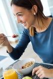 Jeune femme appréciant le petit déjeuner dans la cuisine Photo libre de droits
