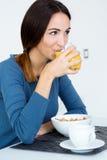 Jeune femme appréciant le petit déjeuner dans la cuisine Images stock