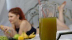 Jeune femme appréciant sur un lit, utilisant l'ordinateur portable et mangeant une banane à la maison pendant le matin Mouvement  clips vidéos